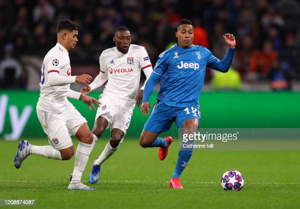 Alex Sandro of Juventus is challenged by Bruno Guimaraes and Thiago Mendes of Olympique Lyon during the UEFA Champions League round of 16 first leg...