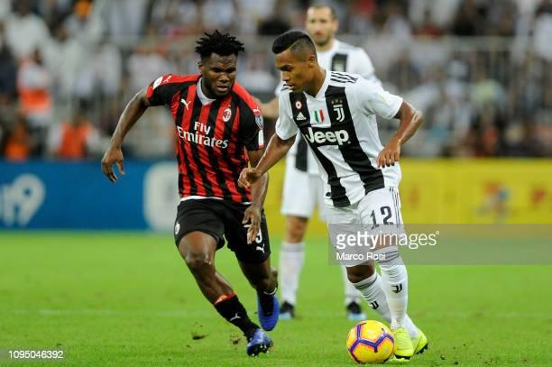 Alex Sandro of Juventus is challenged by Franck Kessie of AC Milan during the Italian Supercup match between Juventus and AC Milan at King Abdullah...