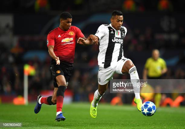 Alex Sandro of Juventus runs with the ball under pressure from Marcus Rashford of Manchester United during the Group H match of the UEFA Champions...