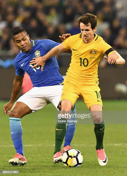 Alex Sandro Silva of Brazil and Robbie Kruse of Australia compete for the ball during the Brasil Global Tour match between Australian Socceroos and...