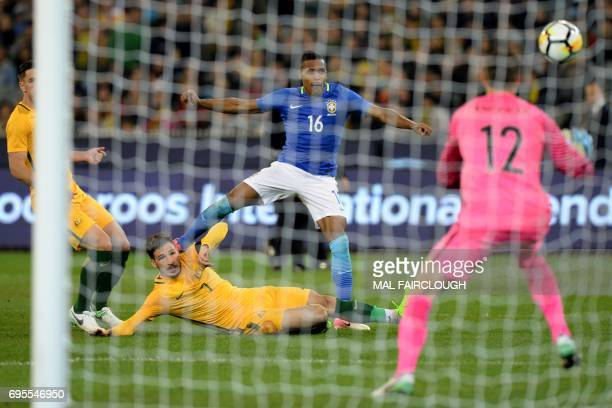 Alex Sandro Silva of Brazil shoots at goal as Mathew Allan Leckie of Australia slides in during the friendly international football match between...