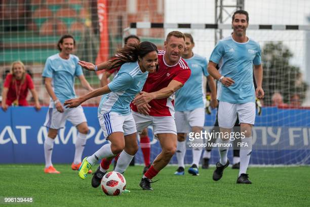 Alex Scott controls the ball against Andrey Tikhonov during the Legends Football Match in Red Square on July 11 2018 in Moscow Russia