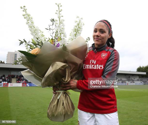 Alex Scott of Arsenal poses with flowers to commemorate her final home game before retirement ahead of the Womens Super League match between Arsenal...