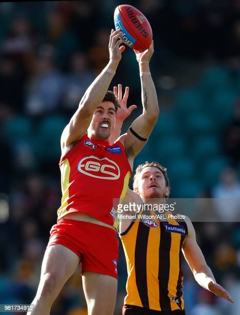 Alex Sexton of the Suns and Blake Hardwick of the Hawks compete for the ball during the 2018 AFL round 14 match between the Hawthorn Hawks and the...