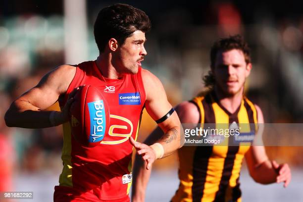Alex Sexton of the Suns kicks the ball from Blake Hardwick of the Hawks during the round 14 AFL match between the Hawthorn Hawks and the Gold Coast...
