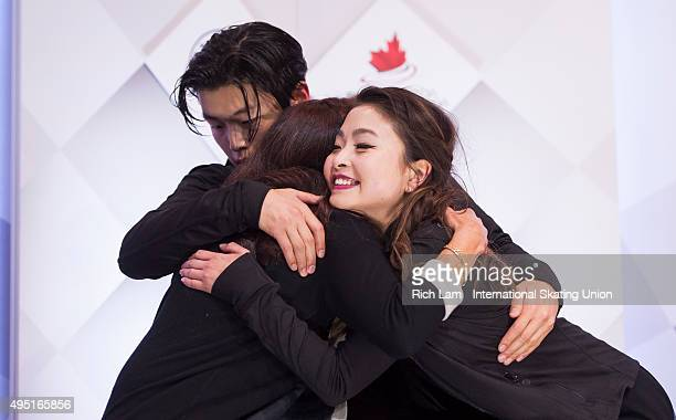Alex Shibutan of the United States hugs his sister and parter Maia and their coach Marina Zueva after getting the results in the Ice Dance Free Dance...