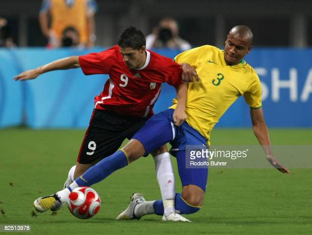 Alex Silva of Brazil and Vincent Kompany of Belgium compete for the ball during the Bronze Medal Match between Belgium and Brazil at Shanghai Stadium...