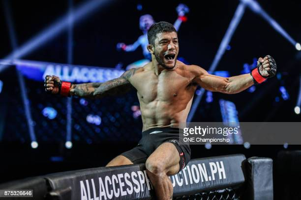 Alex Silva roars in celebration on top of the cage after his submission of Hayato Suzuki during ONE Championship Legends of the World at the Mall of...