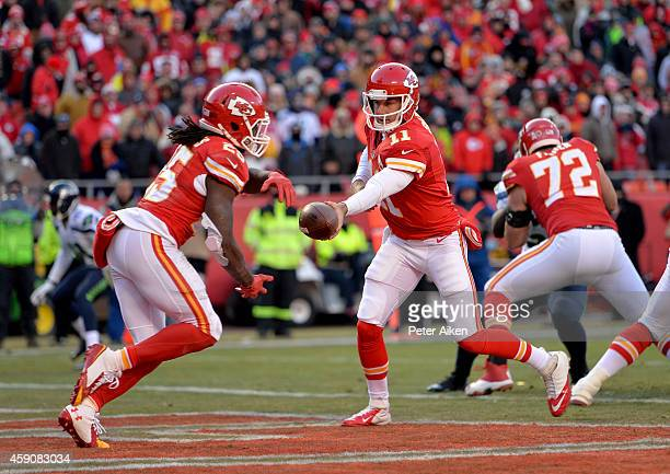 Alex Smith drops back to Jamaal Charles of the Kansas City Chiefs for a run play against the Seattle Seahawks during the game at Arrowhead Stadium on...