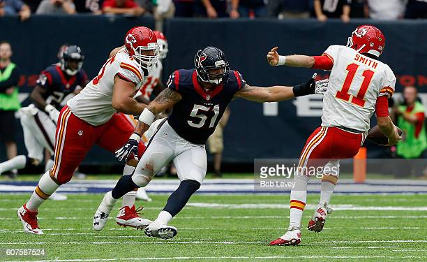 Alex Smith of the Kansas City Chiefs loses his balance as he is pressured by John Simon of the Houston Texans in the fourth quarter at NRG Stadium on...
