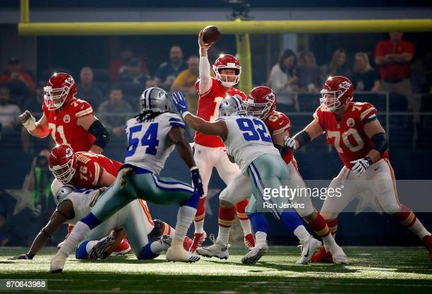 Alex Smith of the Kansas City Chiefs passes the ball under pressure from Jaylon Smith of the Dallas Cowboys and Brian Price of the Dallas Cowboys in...