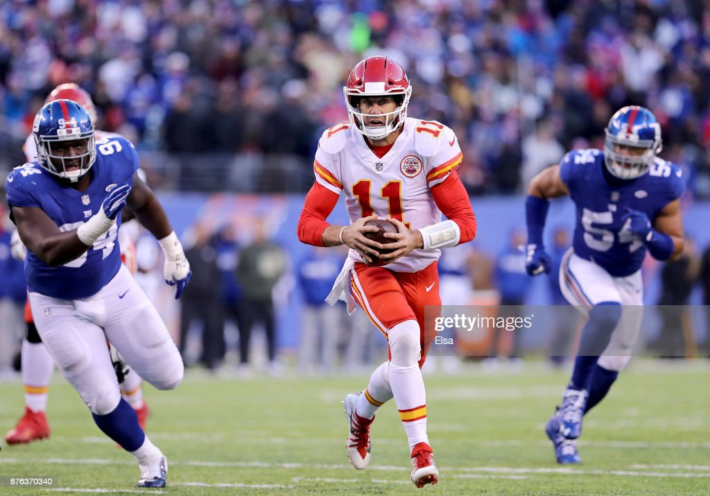Alex Smith #11 of the Kansas City Chiefs scrambles with the ball as Dalvin Tomlinson #94 and Olivier Vernon #54 of the New York Giants defend in the fourth quarter on November 19, 2017 at MetLife Stadium in East Rutherford, New Jersey.
