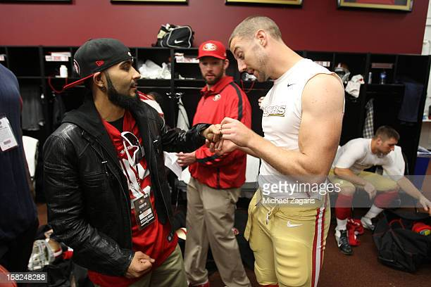 Alex Smith of the San Francisco 49ers checks out the World Series Ring of Sergio Romo from the san Francisco Giants in the locker room following the...
