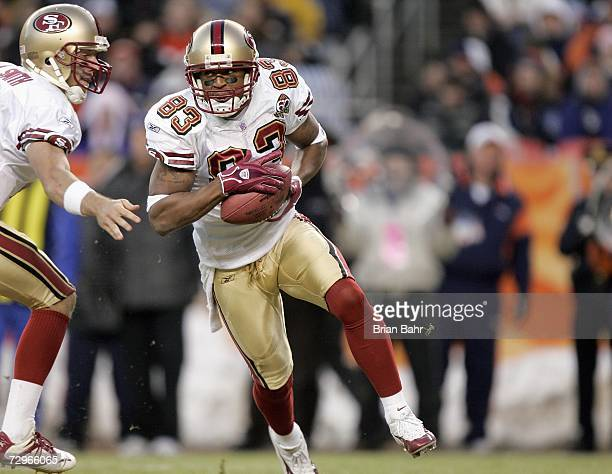 Alex Smith of the San Francisco 49ers hands off the ball to Arnaz Battle during the game against the Denver Broncos at Invesco Field at Mile High on...