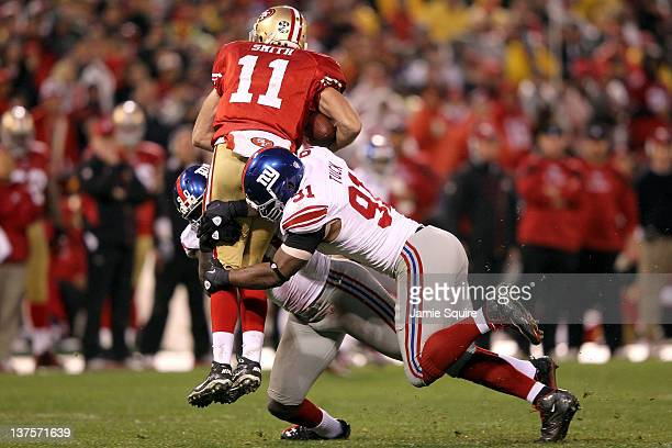 Alex Smith of the San Francisco 49ers is sacked by Justin Tuck and Jason PierrePaul of the New York Giants in the third quarter during the NFC...