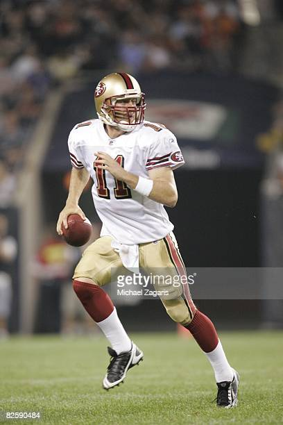 Alex Smith of the San Francisco 49ers looks for an opening during the NFL game against the Chicago Bears at Soldier Field on August 21 2008 in...