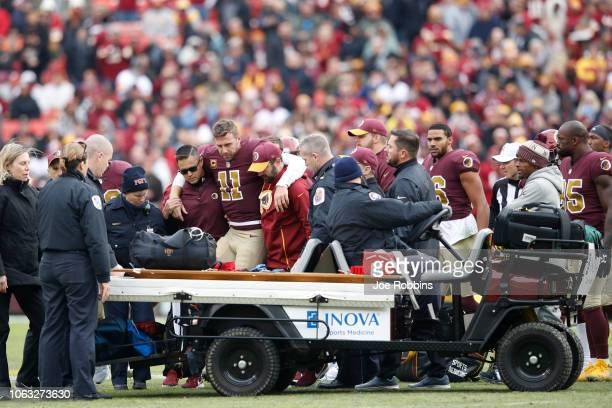 Alex Smith of the Washington Redskins is helped off the field after being sacked and injured by Kareem Jackson of the Houston Texans in the third...