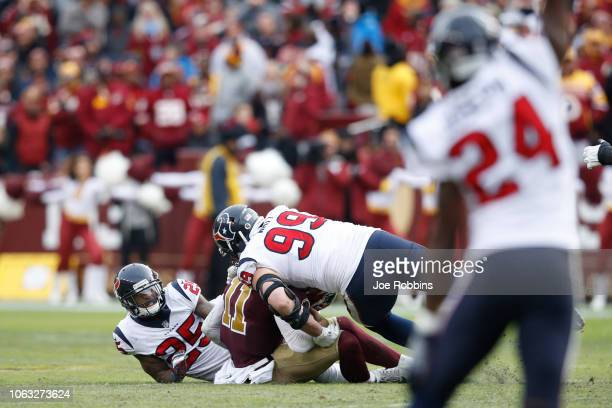 Alex Smith of the Washington Redskins is sacked and injured by Kareem Jackson of the Houston Texans in the third quarter of the game at FedExField on...