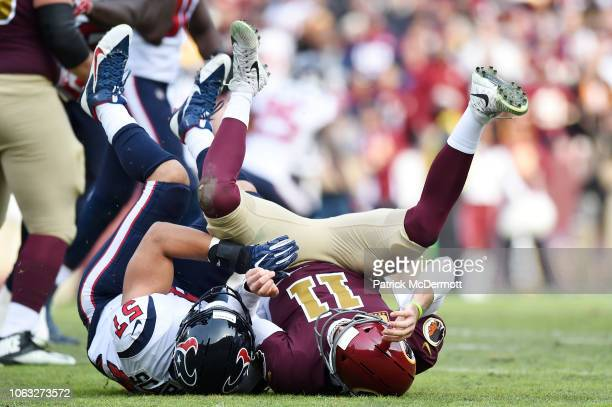 Alex Smith of the Washington Redskins is tackled by Brennan Scarlett of the Houston Texans in the second quarter at FedExField on November 18 2018 in...