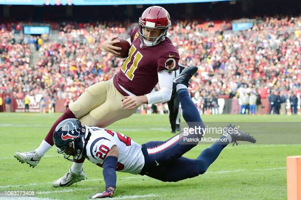 Alex Smith of the Washington Redskins is tackled by Justin Reid of the Houston Texans in the first half at FedExField on November 18 2018 in Landover...