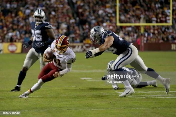 Alex Smith of the Washington Redskins is tackled by Tyrone Crawford of the Dallas Cowboys during the second half at FedExField on October 21 2018 in...