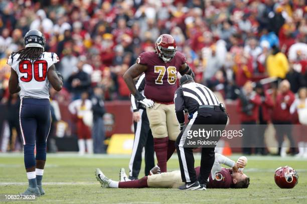 Alex Smith of the Washington Redskins lays on the field after being sacked and injured by Kareem Jackson of the Houston Texans in the third quarter...