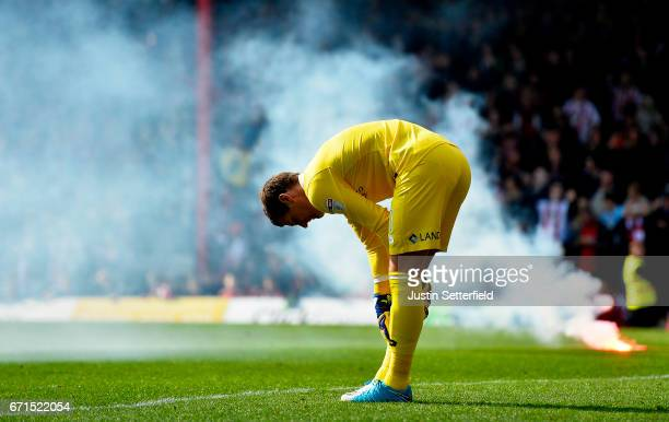 Alex Smithies of Queens Park Rangers reacts as a flare burns behind him during the Sky Bet Championship match between Brentford and QPR at Griffin...