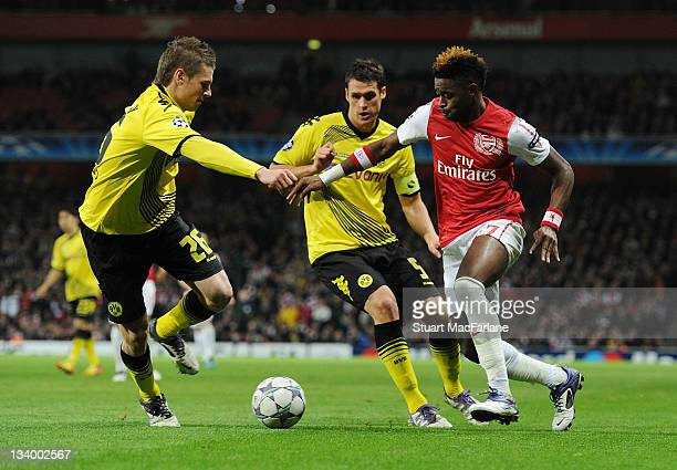Alex Song breaks past Lucasz Piszczek and Sebastian Kehl on his way to setting up Robin van Persie for the 1st Arsenal goal during the UEFA Champions...