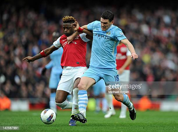Alex Song of Arsenal fights for the ball with Gareth Barry of Man City during the Barclays Premier League match between Arsenal and Manchester City...
