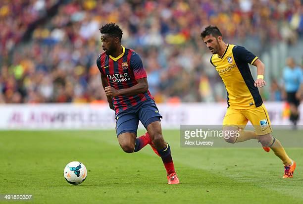 Alex Song of FC Barcelona beats David Villa of Club Atletico de Madrid during the La Liga match between FC Barcelona and Club Atletico de Madrid at...