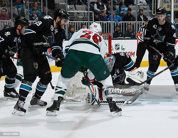 Alex Stalock and Barclay Goodrow of the San Jose Sharks protect the net against Thomas Vanek of the Minnesota Wild during an NHL game on December 11...