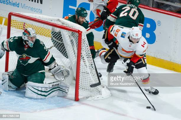 Alex Stalock of the Minnesota Wild defends against Sam Bennett of the Calgary Flames during the game at the Xcel Energy Center on December 12 2017 in...