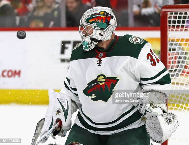 Alex Stalock of the Minnesota Wild keeps an eye on the puck after knocking it away against the Chicago Blackhawks at the United Center on December 17...