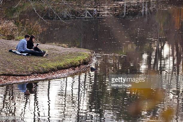 Alex Tague and Julie Young tourists from London sit along side the lake during the mild autumn weather in Prospect Park on November 27 2011 in the...