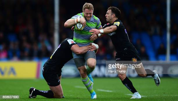 Alex Tait of Newcastle Falcons is tackled by Ian Whitten of Exeter Chiefs and Nic White of Exeter Chiefs during the Aviva Premiership match between...
