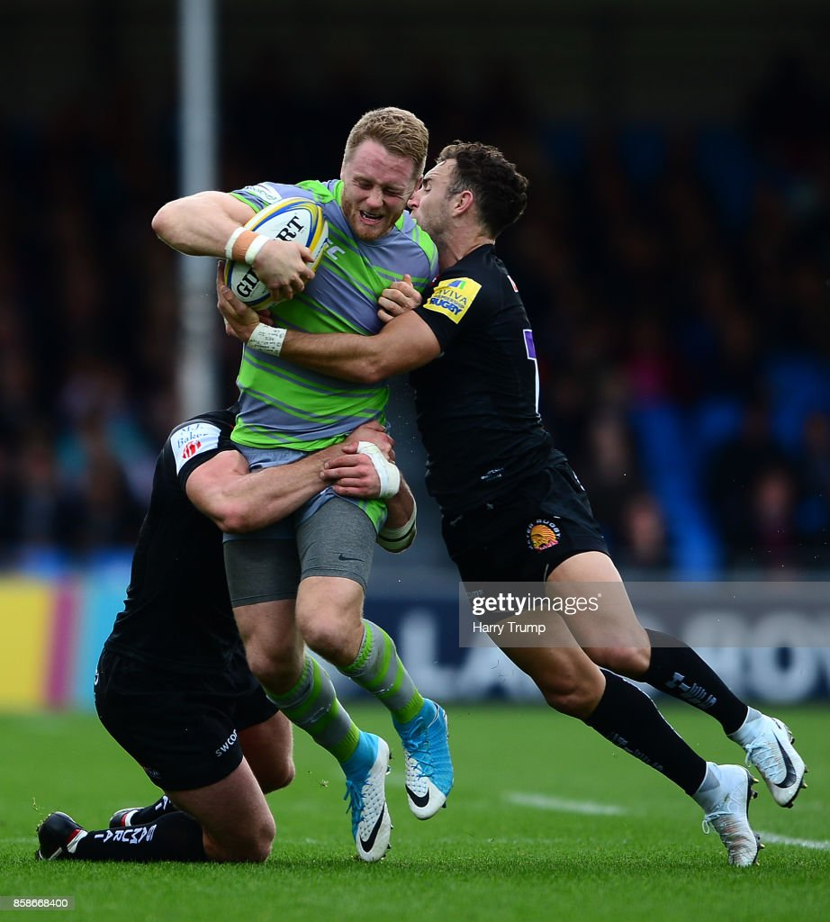 Alex Tait of Newcastle Falcons is tackled by Ian Whitten of Exeter Chiefs(L) and Nic White of Exeter Chiefs during the Aviva Premiership match between Exeter Chiefs and Newcastle Falcons at Sandy Park on October 7, 2017 in Exeter, England.