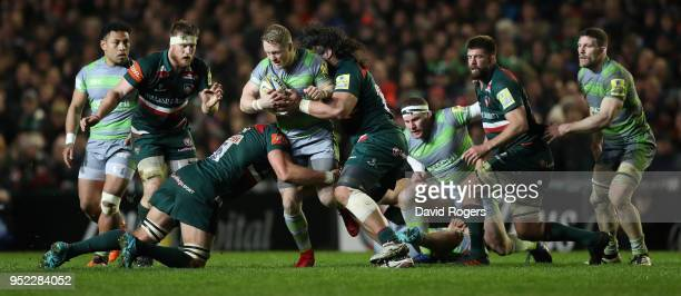 Alex Tait of Newcastle Falcons is tackled during the Aviva Premiership match between Leicester Tigers and Newcastle Falcons at Welford Road on April...