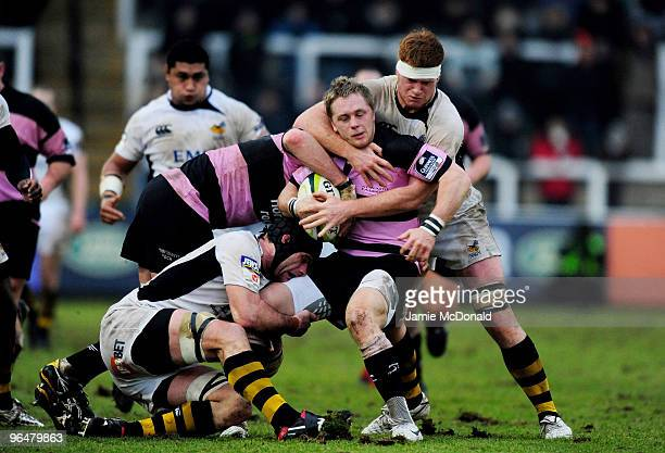 Alex Tait of Newcastle is tackled by Hugo Ellis and Marty Veale of Wasps during the LV Anglo Welsh Cup match between Newcastle Falcons and London...