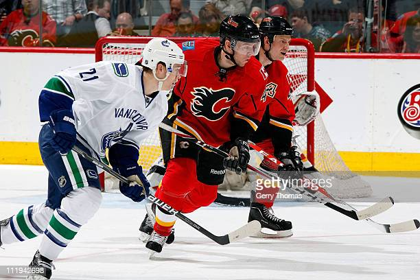 Alex Tanguay and Jay Bouwmeester of the Calgary Flames skate against Mason Raymond of the Vancouver Canucks on April 9 2011 at the Scotiabank...