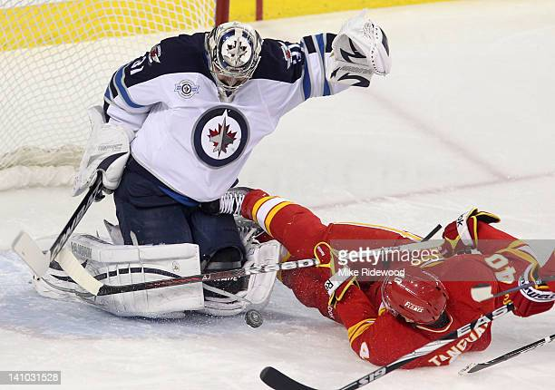 Alex Tanguay of the Calgary Flames and the puck slide into Ondrej Pavelec of the Winnipeg Jets in firstperiod NHL action on March 9 2012 at the...