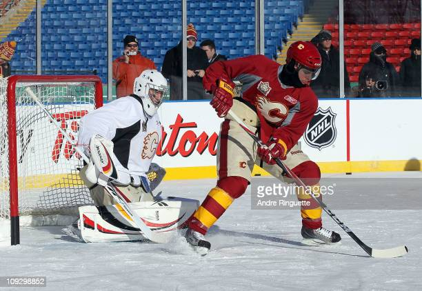 Alex Tanguay of the Calgary Flames spins with the puck in front of Henrik Karlsson during the practice session the day before the 2011 NHL Heritage...