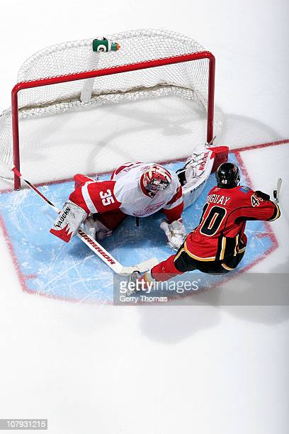 Alex Tanguay of the Calgary Flames tries to deke around Jimmy Howard of the Detroit Red Wings during a shootout on January 07 2011 at the Scotiabank...