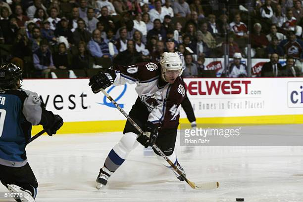 Alex Tanguay of the Colorado Avalanche passes the puck back to Rob Blake for an assist rather than shooting on goalie Evgeni Nabokov of the San Jose...