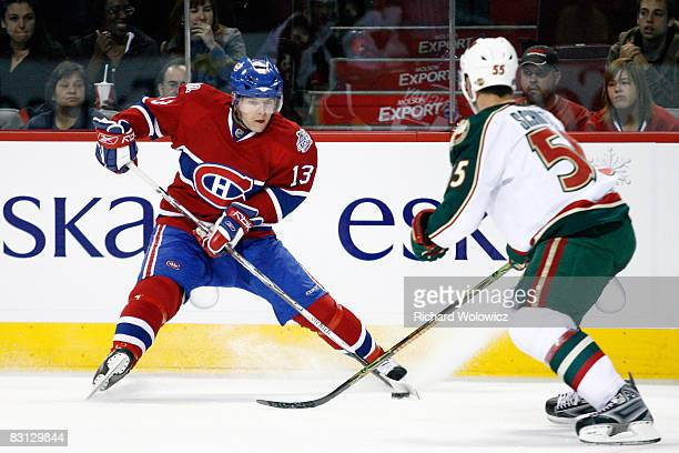 Alex Tanguay of the Montreal Canadiens stops withe puck in front of Nick Schultz of the Minnesota Wild during the game at the Bell Centre on October...