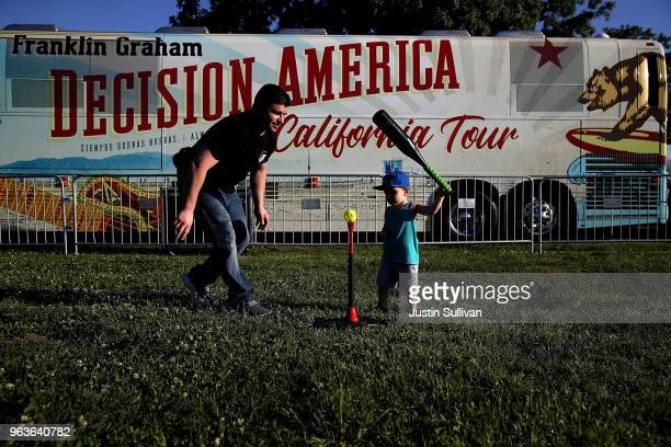 Alex Tapia plays ball with his two yearold son Dominic Tapia as they wait for the start of Franklin Graham's 'Decision America' California tour at...