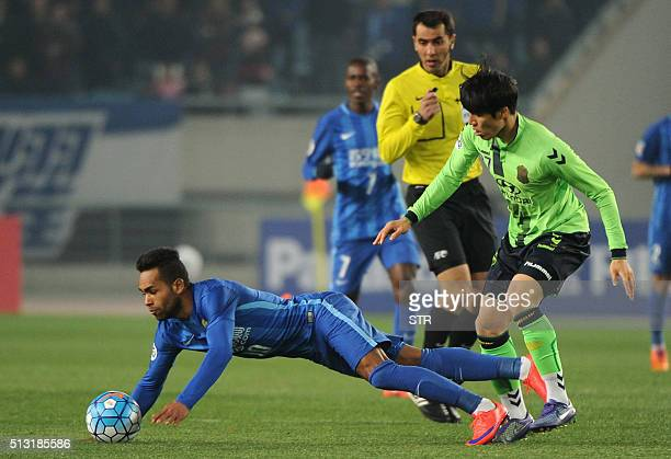 Alex Teixeira of China's Jiangsu FC falls as he fights for the ball with Kim Jangsoo of South Korea's Jeonbuk during their AFC Champions League group...