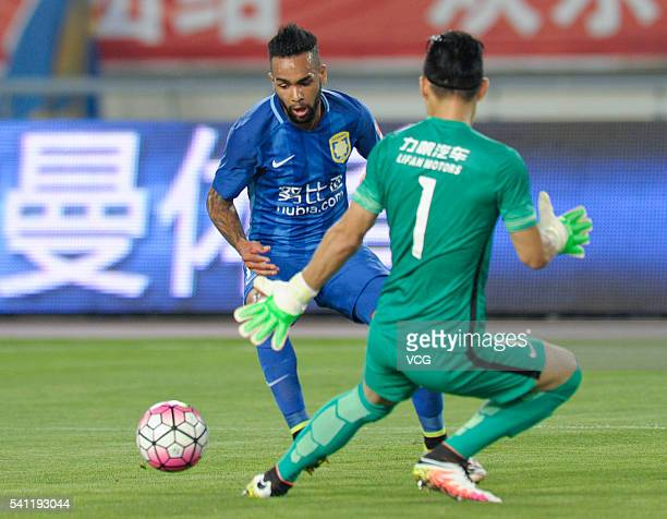 Alex Teixeira of Jiangsu Suning and goalkeeper Deng Xiaofei of Chongqing Lifan compete for the ball during the Chinese Football Association Super...