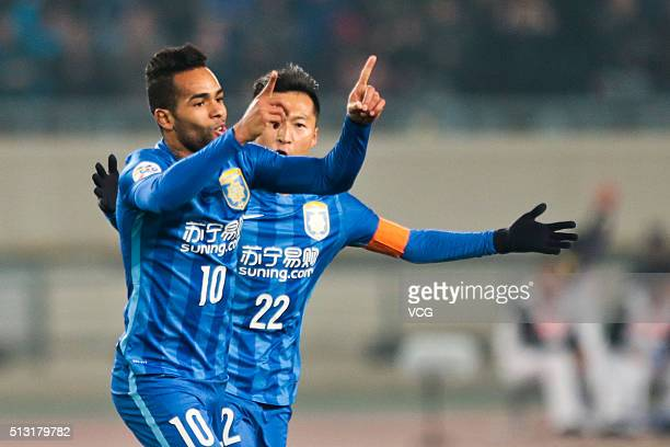 Alex Teixeira of Jiangsu Suning celebrates with team mates after scoring his team's first goal during the AFC Champions League Group E match between...