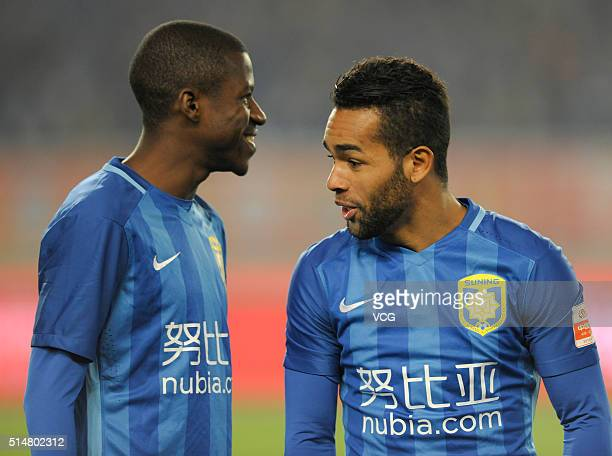 Alex Teixeira of Jiangsu Suning speaks with Ramires during the Chinese Football Association Super League match between Jiangsu Suning and Yanbian...