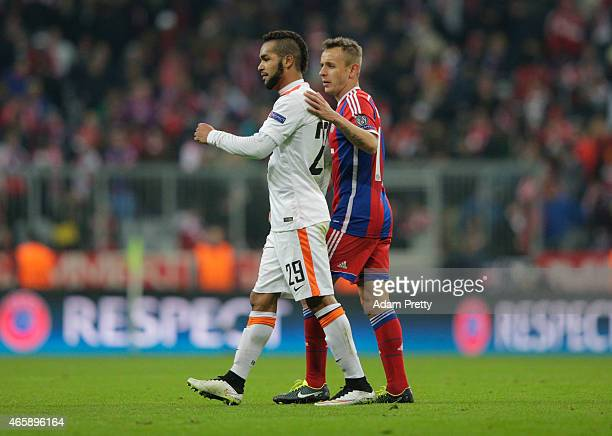 Alex Teixeira of Shakhtar Donetsk is consoled by Rafinha of Bayern Muenchen during the UEFA Champions League Round of 16 second leg match between FC...